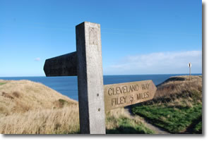 signpost at the top of path down to Cayton Bay
